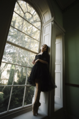 a woman wearing ballerina slippers standing in the frame of a window