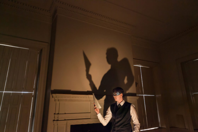 a person standing in a dimly lit room holding a letter