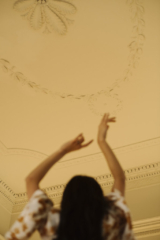 a woman with her arms up looking at the ceiling plasterwork