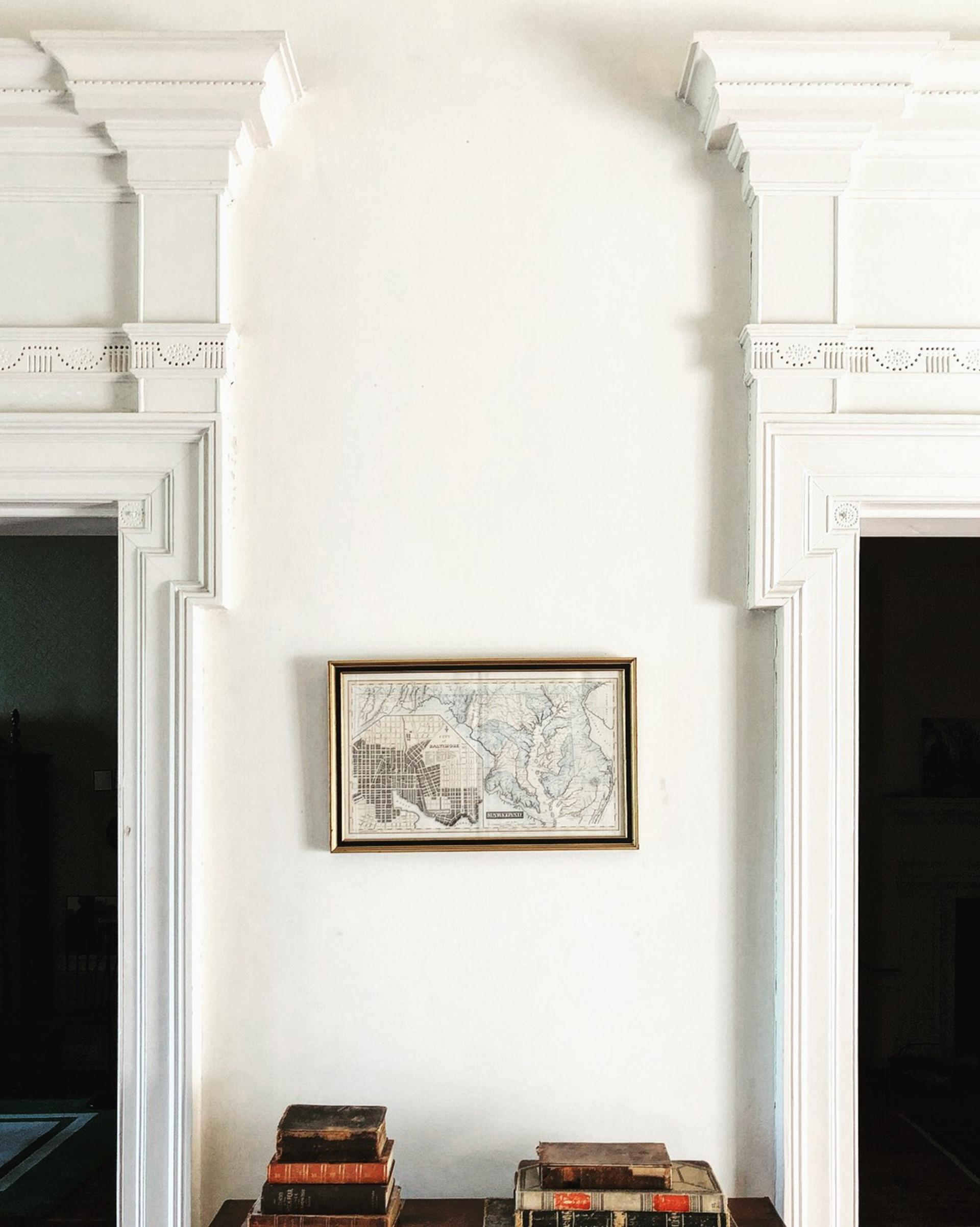 a framed historic map hanging on the wall between two doorways