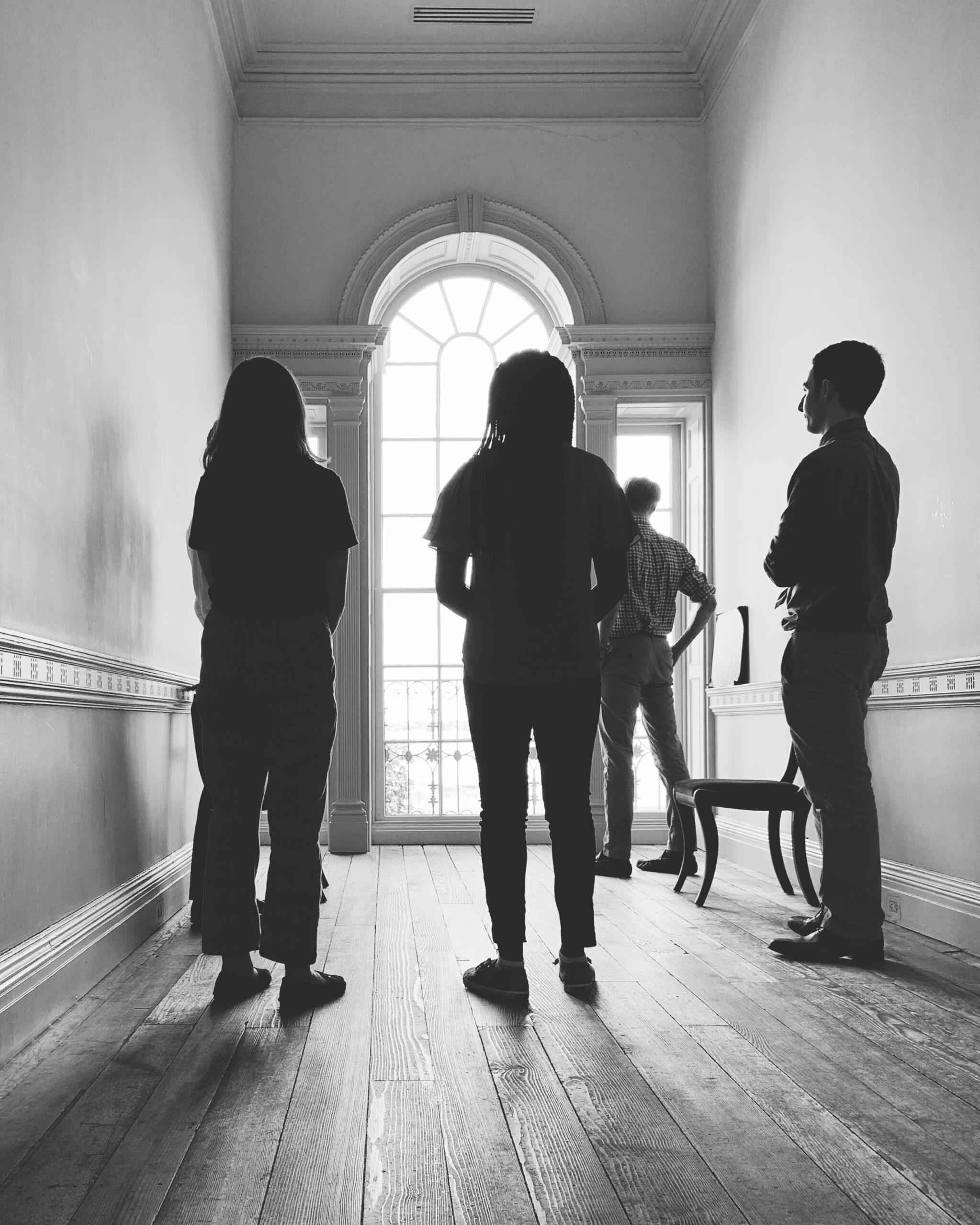 black-and-white photo of a group of people facing a window