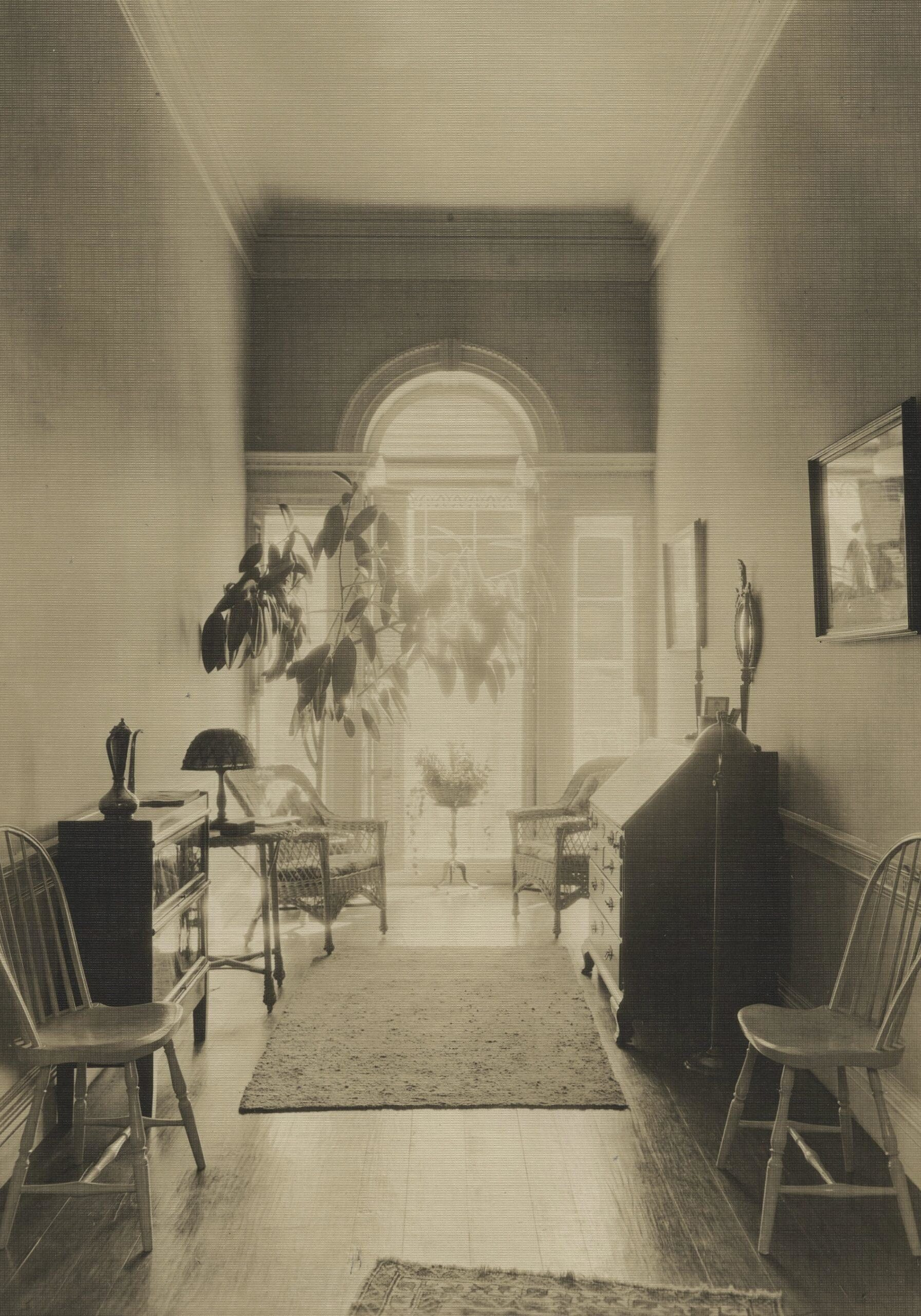 black-and-white photo looking down a hallway with furniture along the walls